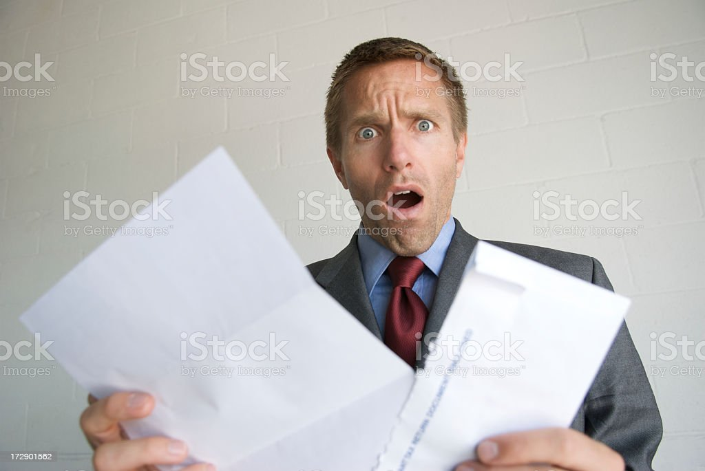 Young Man Businessman Opening Letter with Shocked Expression stock photo