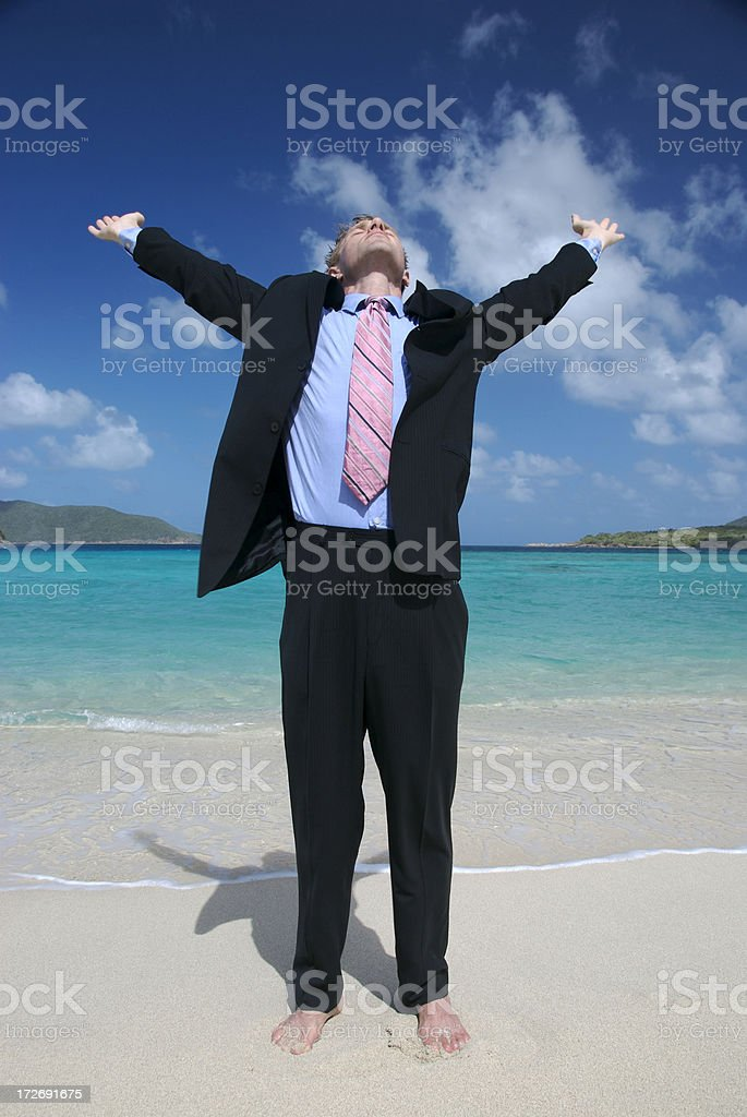 Young Man Businessman Stretching on Tropical Beach in Suit royalty-free stock photo