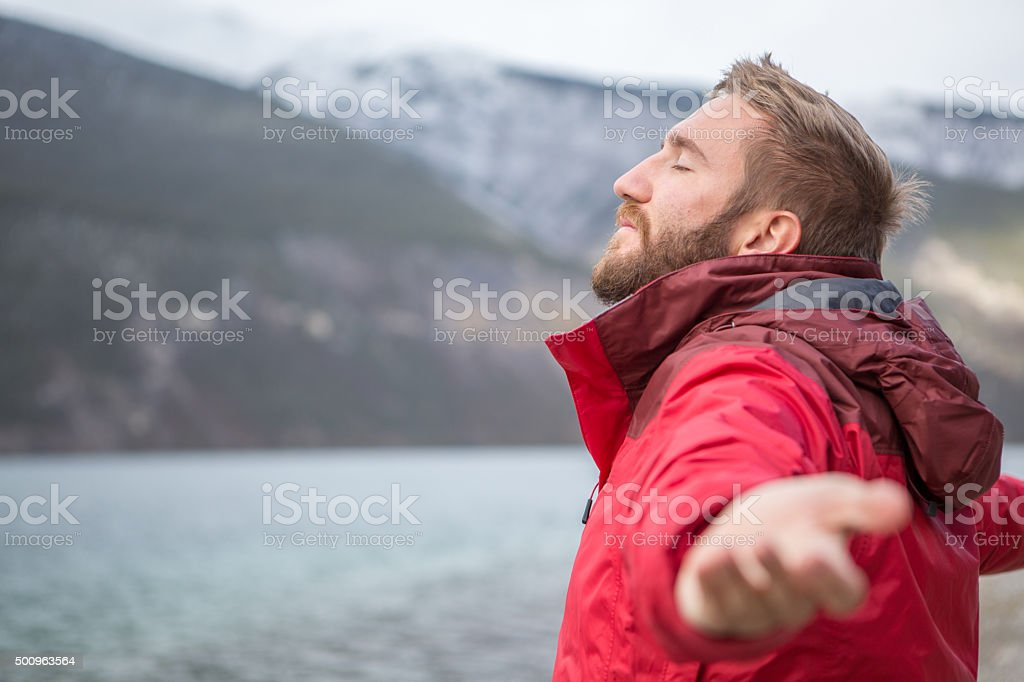 Young man by the lake arms outstretched for relaxation stock photo
