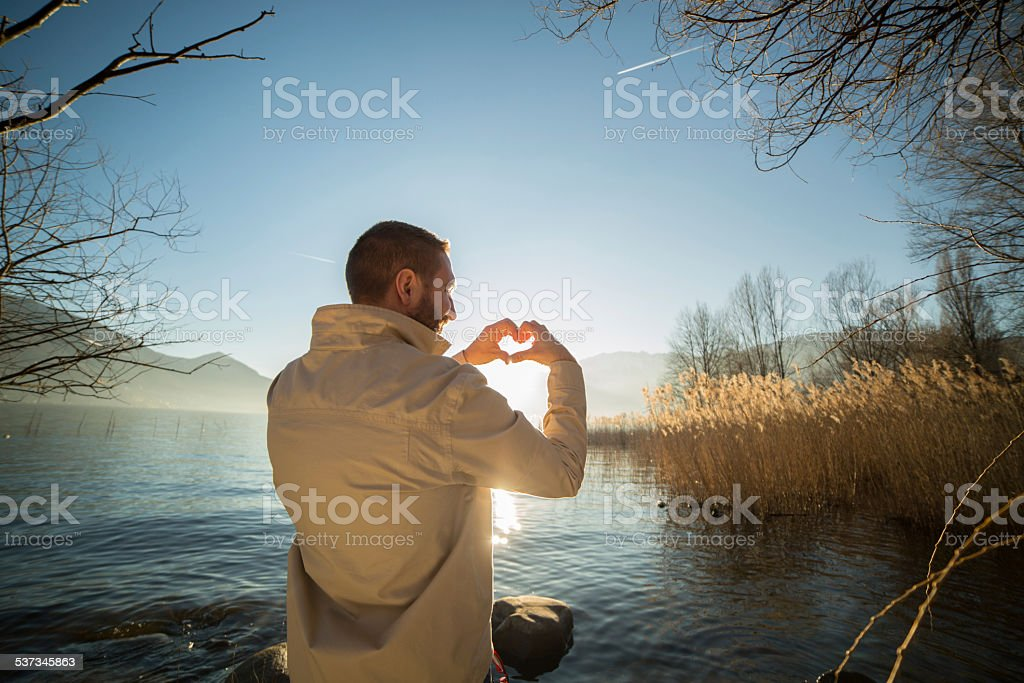 Young man by the lake loving the nature stock photo