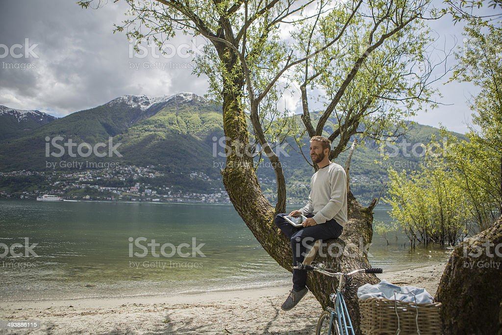 Junger Mann am See mit digitalen tablet – Foto