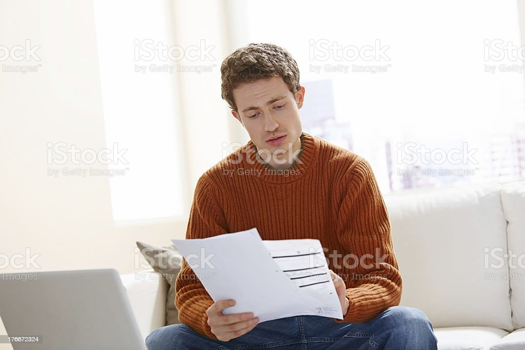 Image of young man going through his monthly expenses bills at home