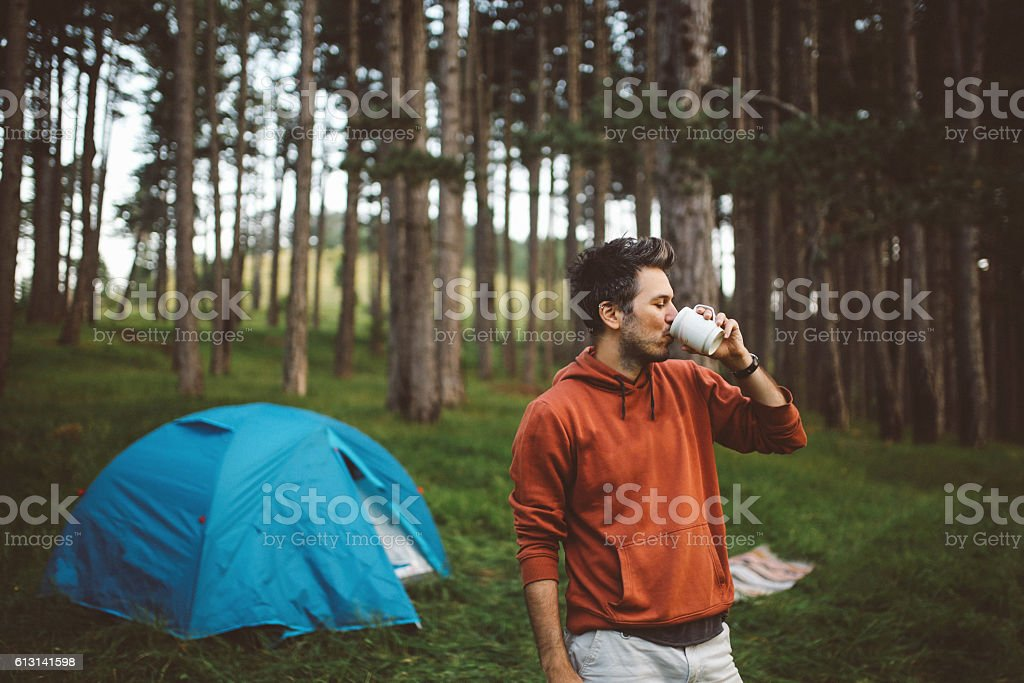 Young man camping in the forest stock photo