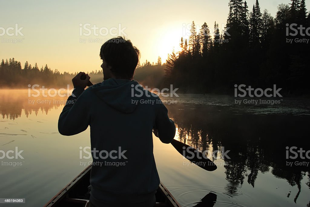 Young man canoeing at sunrise stock photo