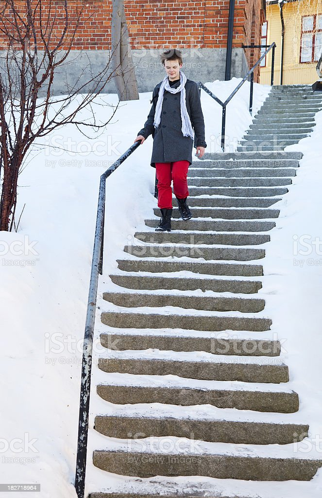 Young man carefully walking on snowy staircase in the winter royalty-free stock photo