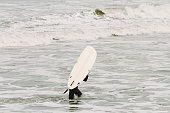 Young man carries a surfboard as he leaves the sea
