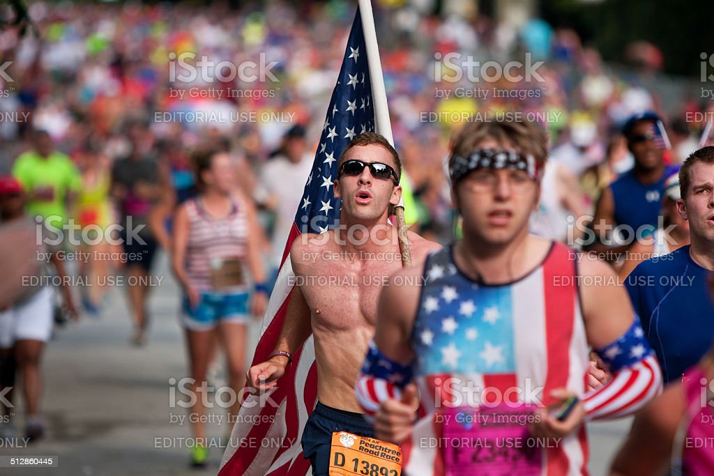 Young Man Carries Large American Flag In Atlanta 10K Race stock photo
