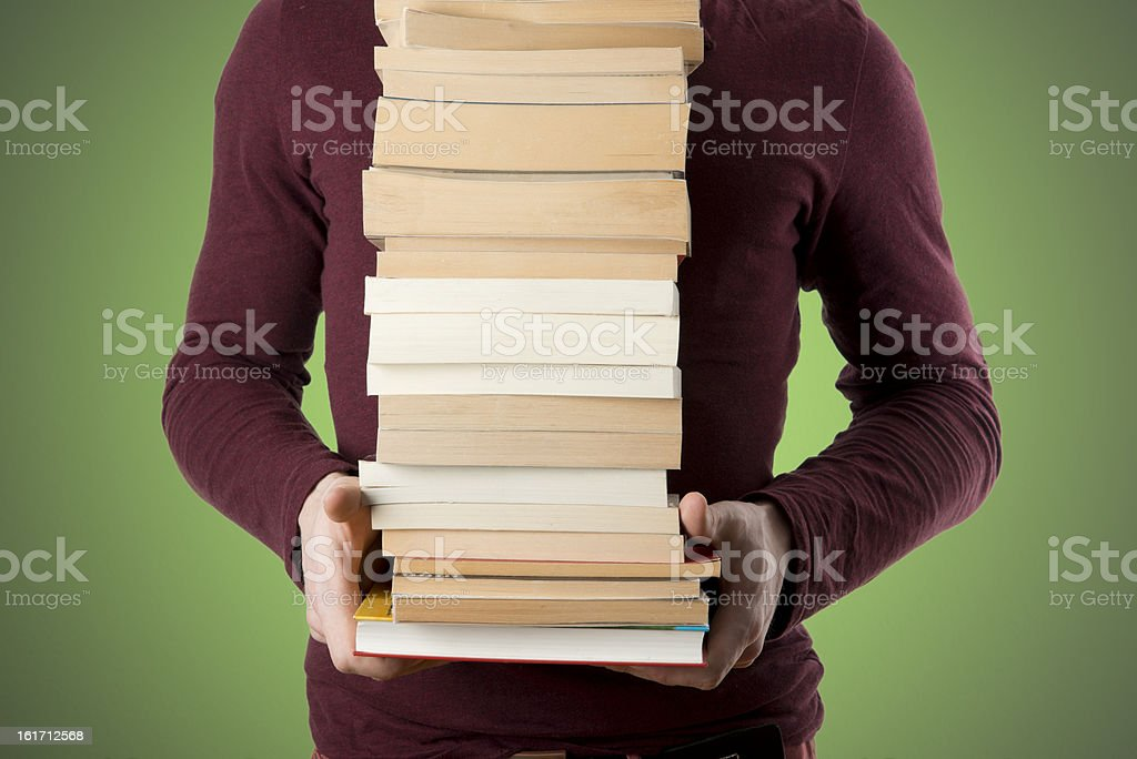 young man carrying book stack on green background stock photo