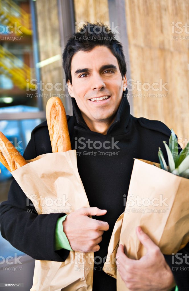 Young Man Carrying Brown Bag Groceries Outside royalty-free stock photo