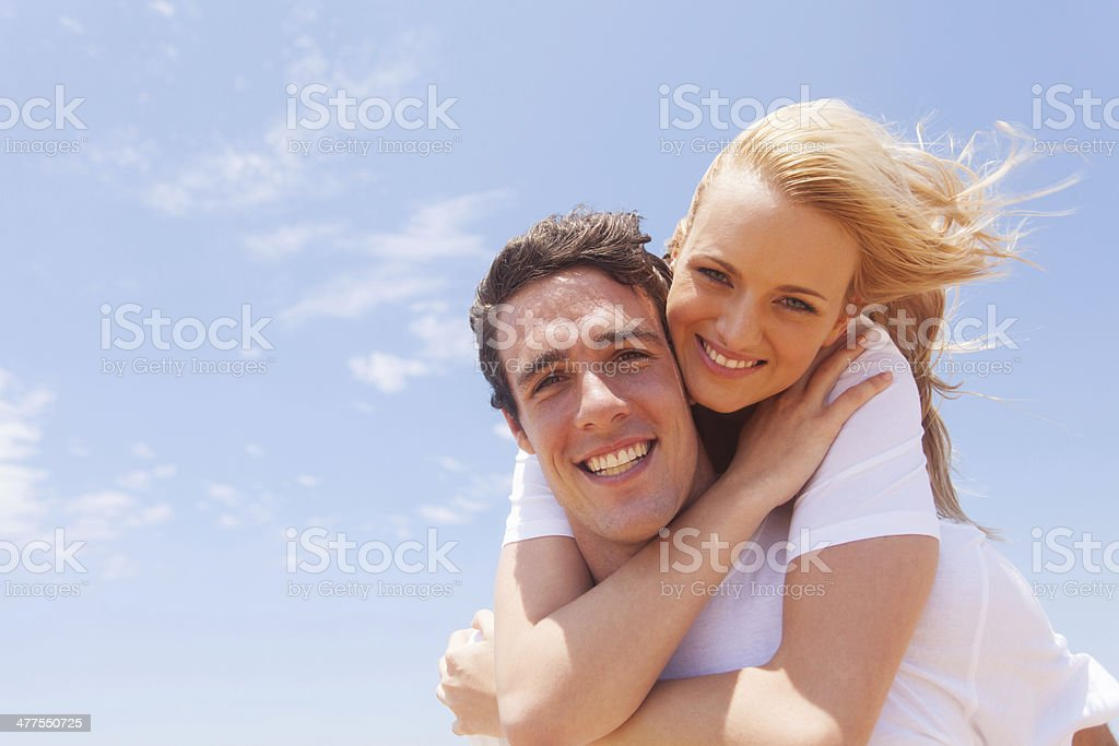 young man carrying girlfriend on his back royalty-free stock photo