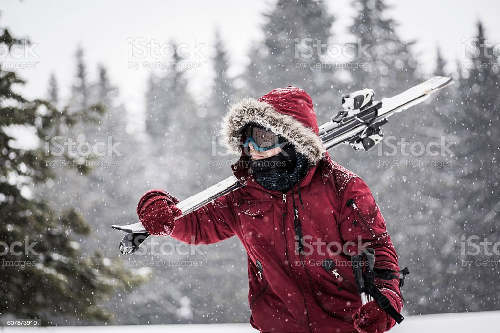 Young man carrying skis through snowy forest stock photo