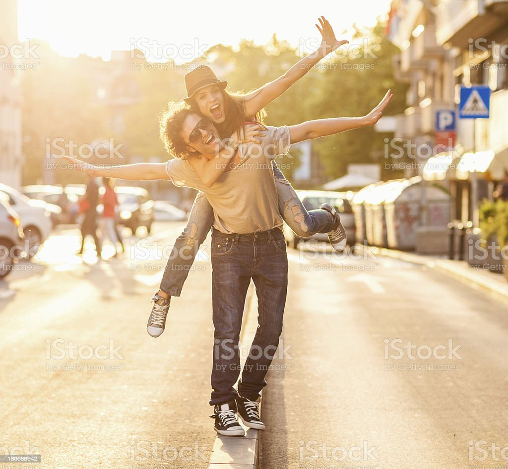 Young man carrying young woman on his back outside stock photo