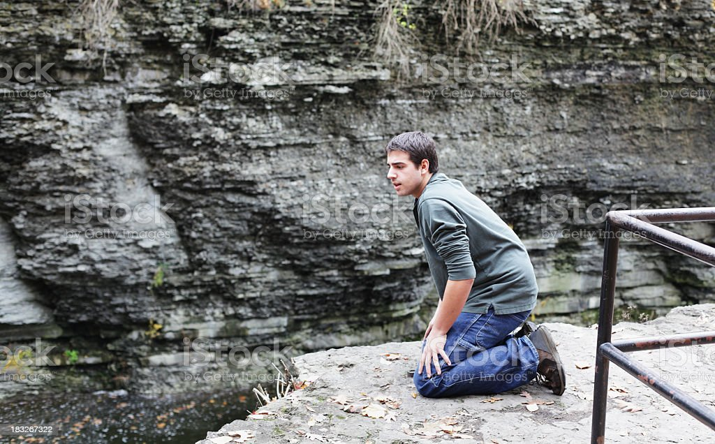Young Man Cautiously Kneeling at Edge of Steep River Gorge stock photo