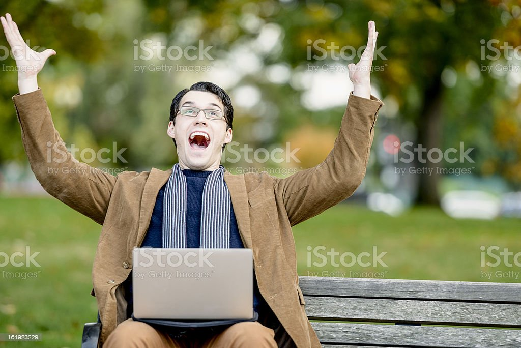 Young Man Celebrating With Laptop On Park Bench royalty-free stock photo