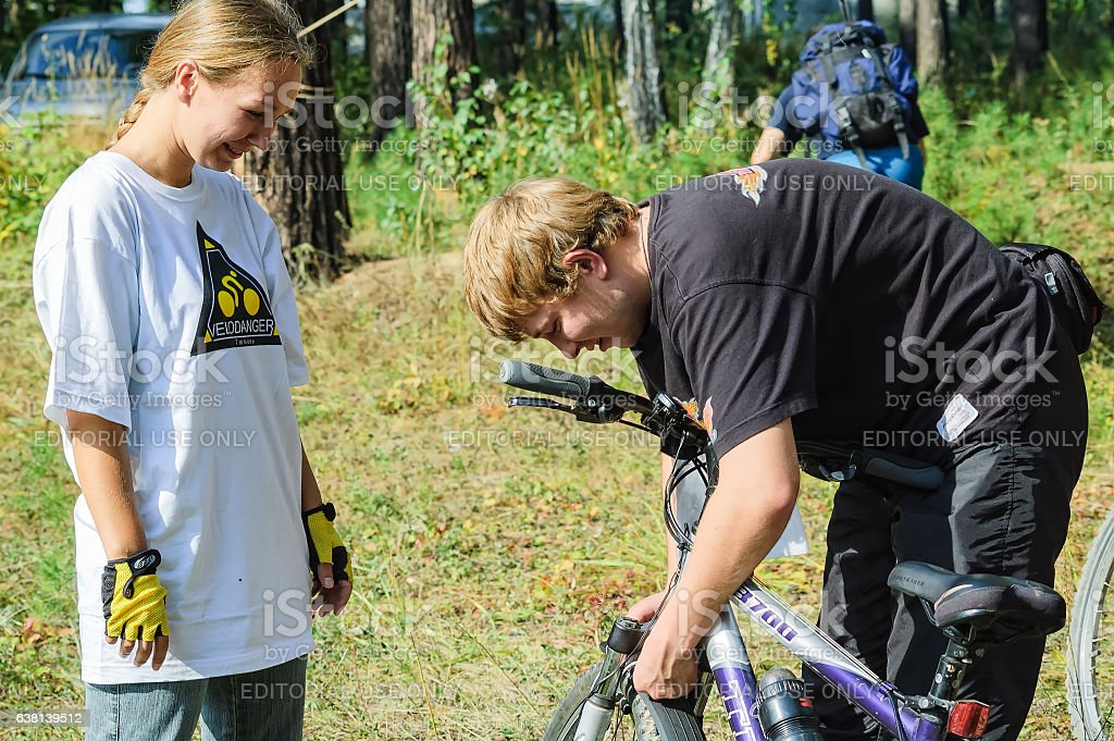 Young man checking bicycle of girl stock photo