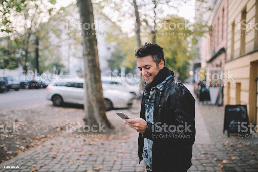 Young man checking cellphone in Berlin Prenzlauer Berg stock photo
