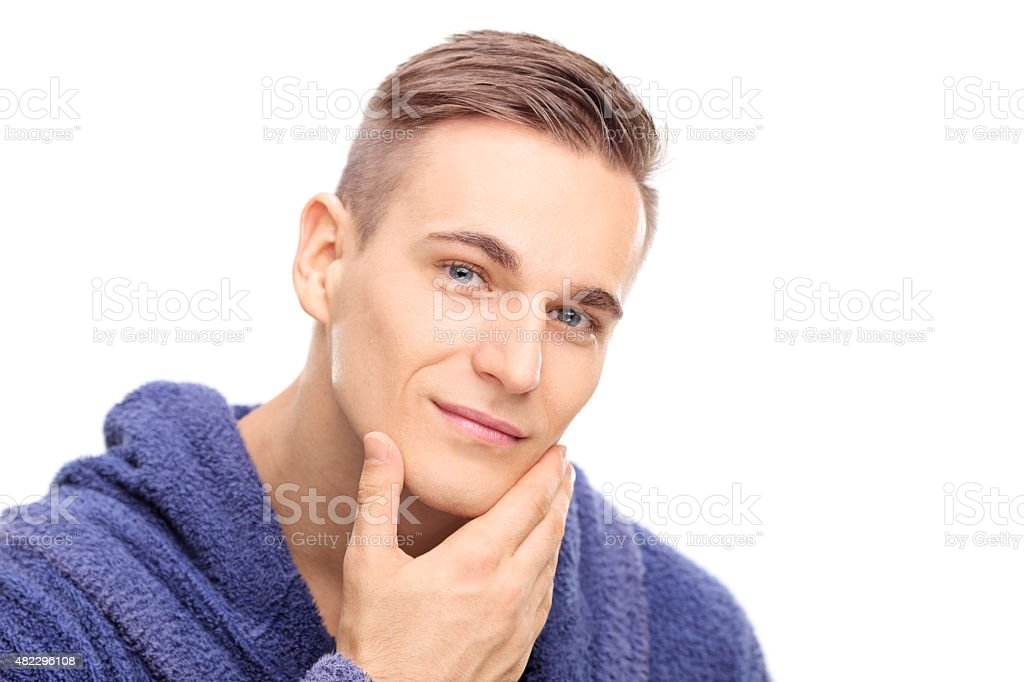 Young man checking the skin on his face stock photo