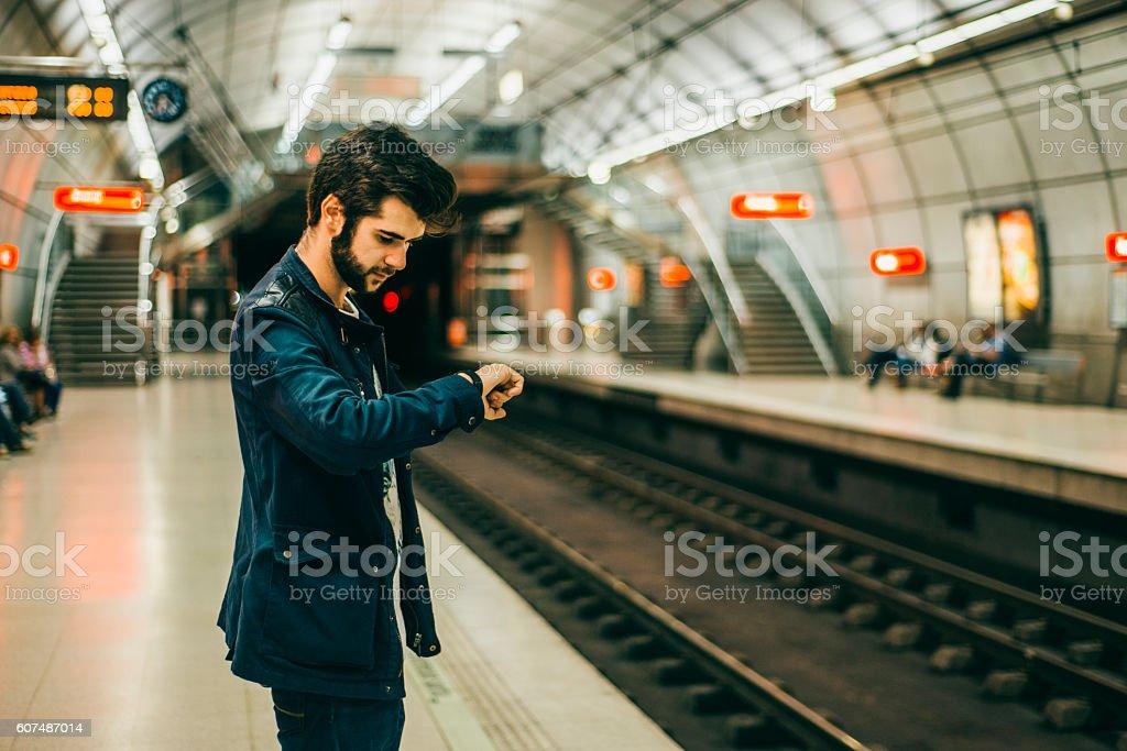 Young man checking wristwatch stock photo
