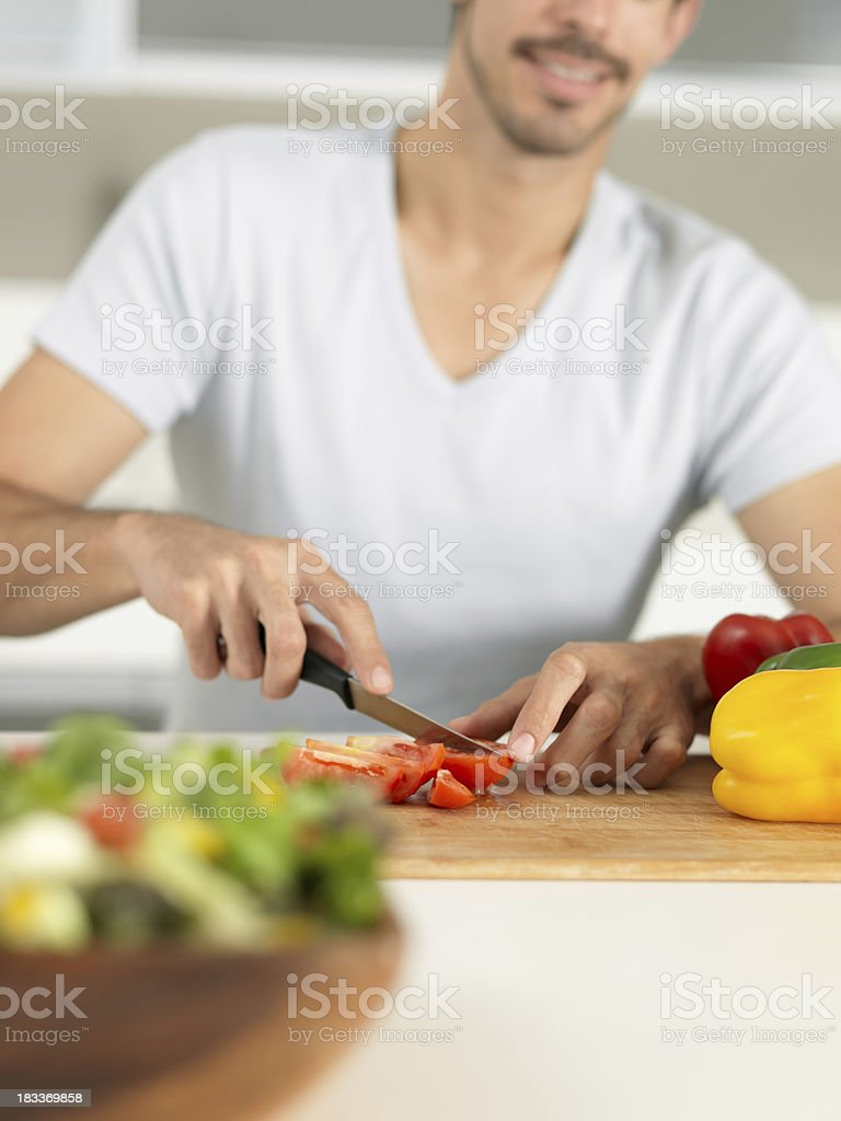 Young man chopping vegetables royalty-free stock photo