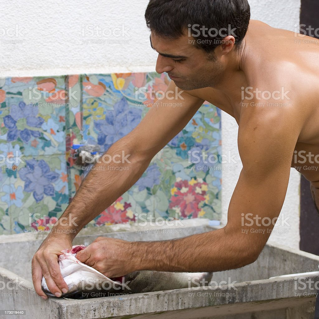young man cleaning a fresh bass royalty-free stock photo