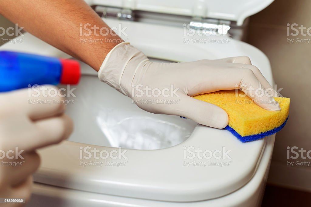 young man cleaning a toilet stock photo
