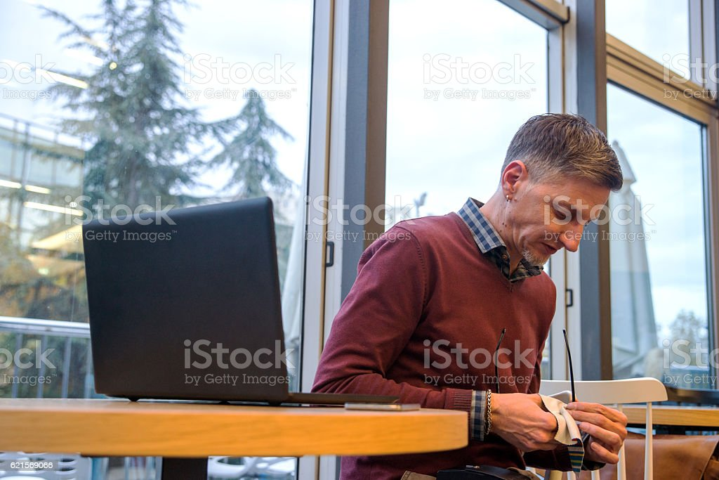young man cleaning his eyeglasses stock photo