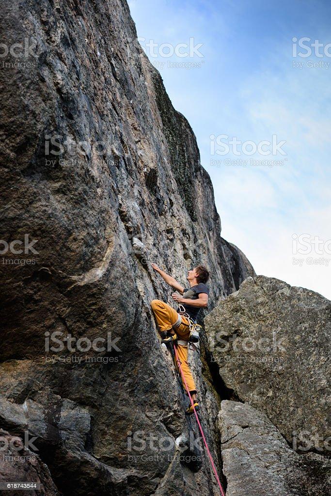 Young man climbing a rock, outdoors. stock photo
