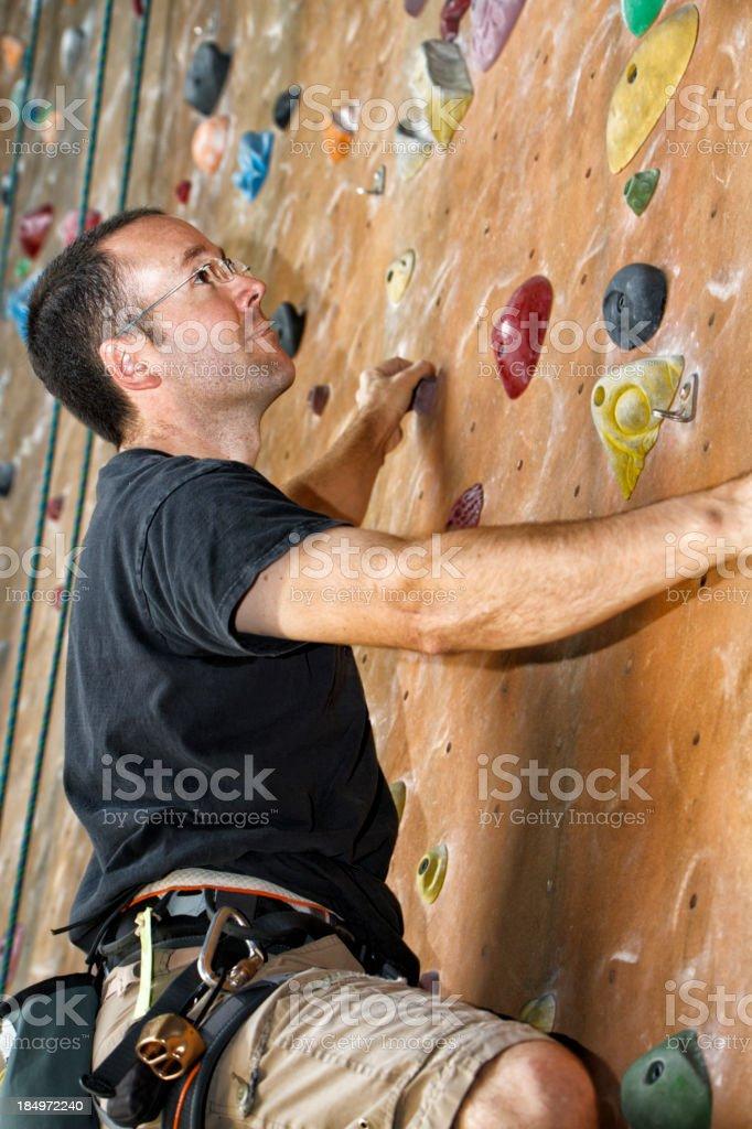 Young Man Climbing An Indoor Rock Wall stock photo