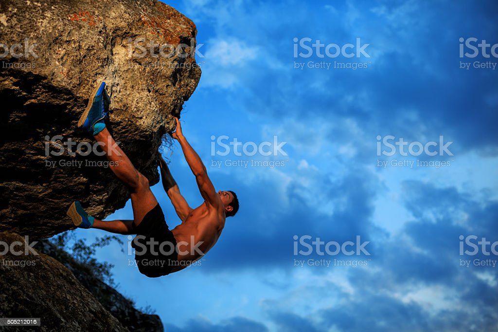 Young man climbing on a wall stock photo