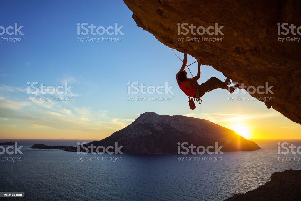 Young man climbing overhanging cliff at sunset stock photo