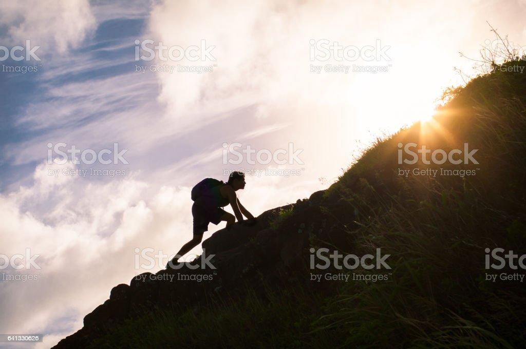 Young man climbing up a mountain. stock photo