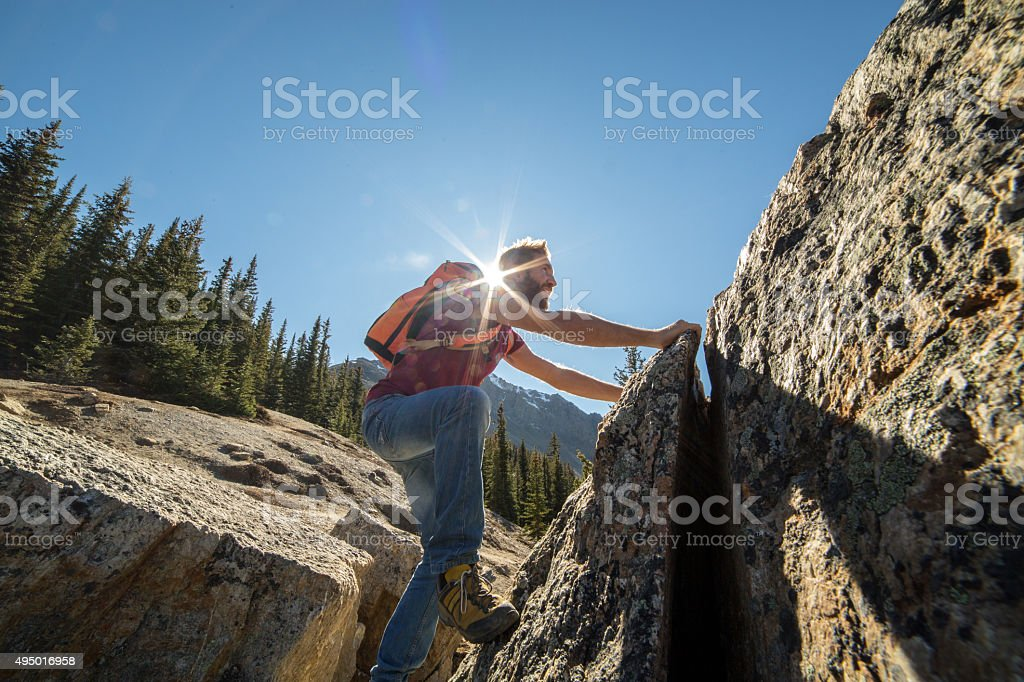 Young man climbs steep rock, moving up stock photo