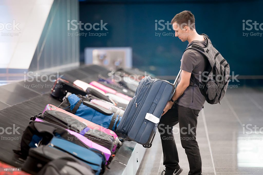 Young man collecting his luggage stock photo