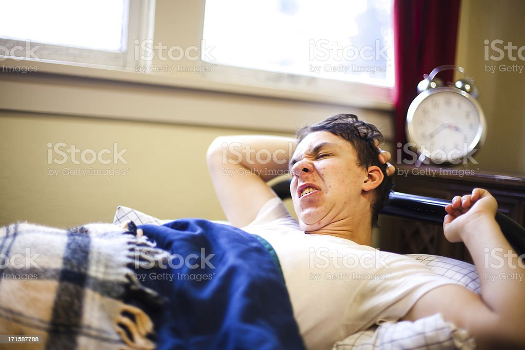 Young Man College Student Struggles Waking Up Early in Morning royalty-free stock photo