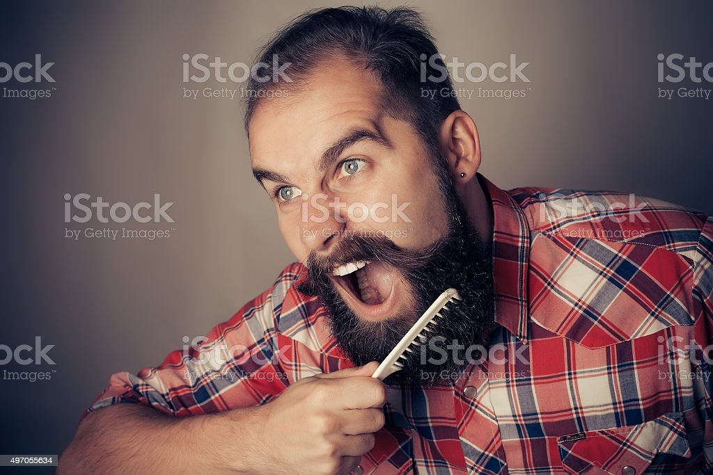 young man comb his beard and moustache on gray background stock photo