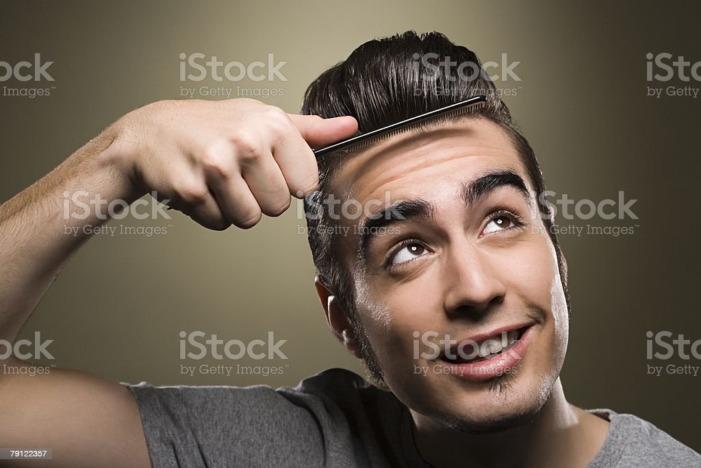 Young man combing his quiff stock photo