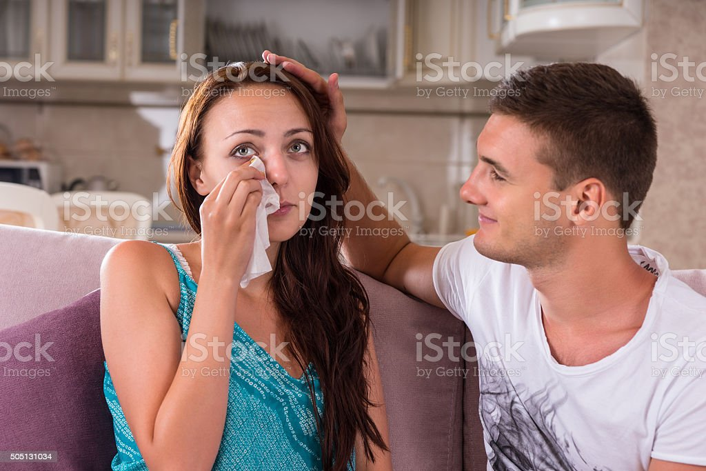 Young Man Comforting Emotional Woman at Home stock photo