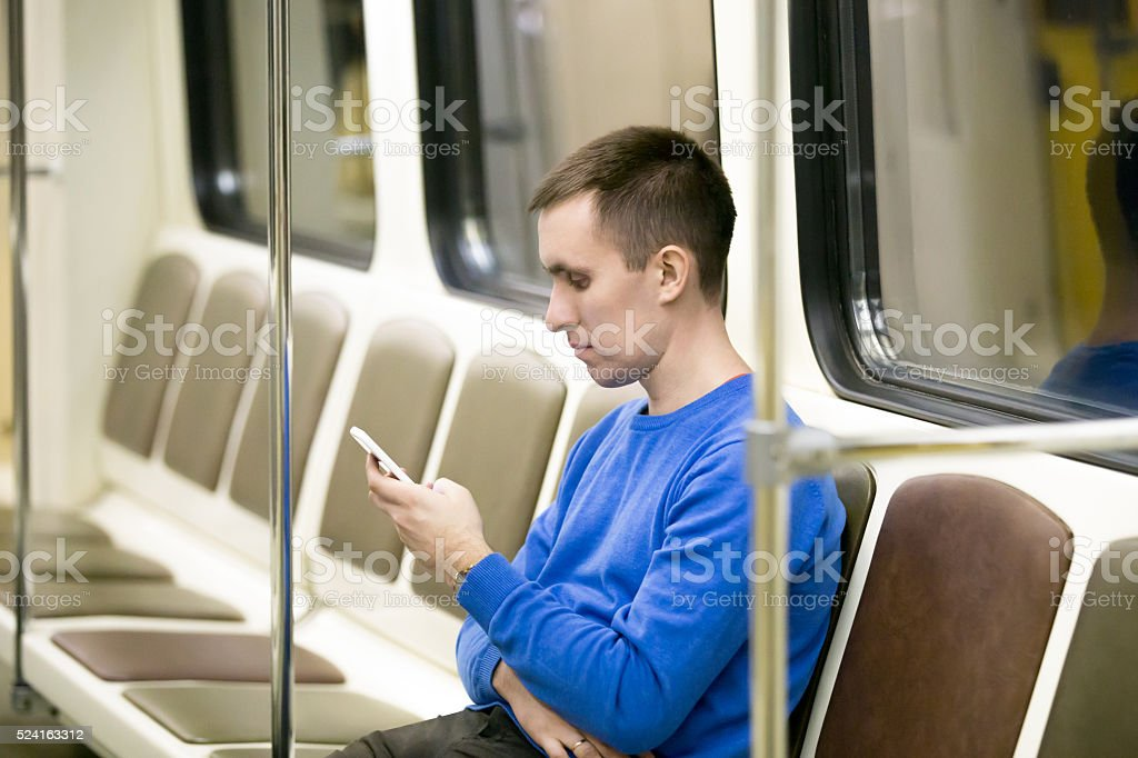 Young man commuting by subway train stock photo