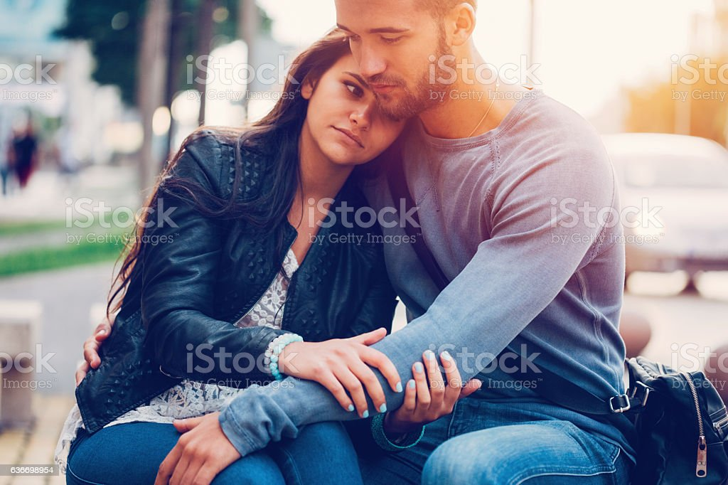Young man consoling his girlfriend stock photo