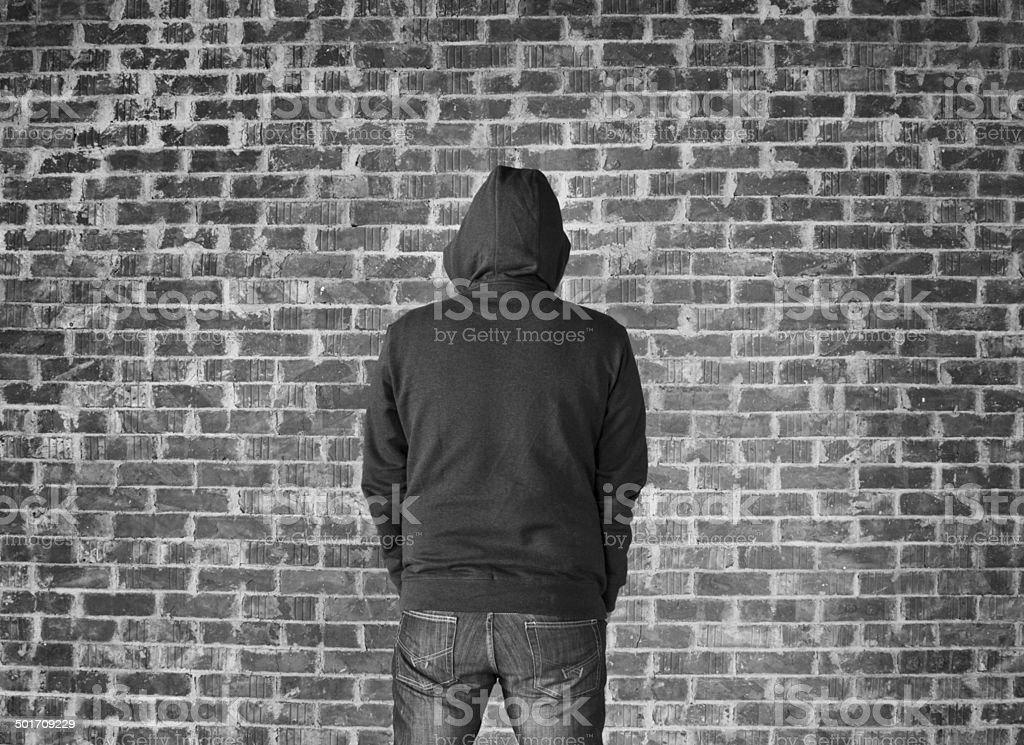 Young man covered his head against wall,black and white stock photo