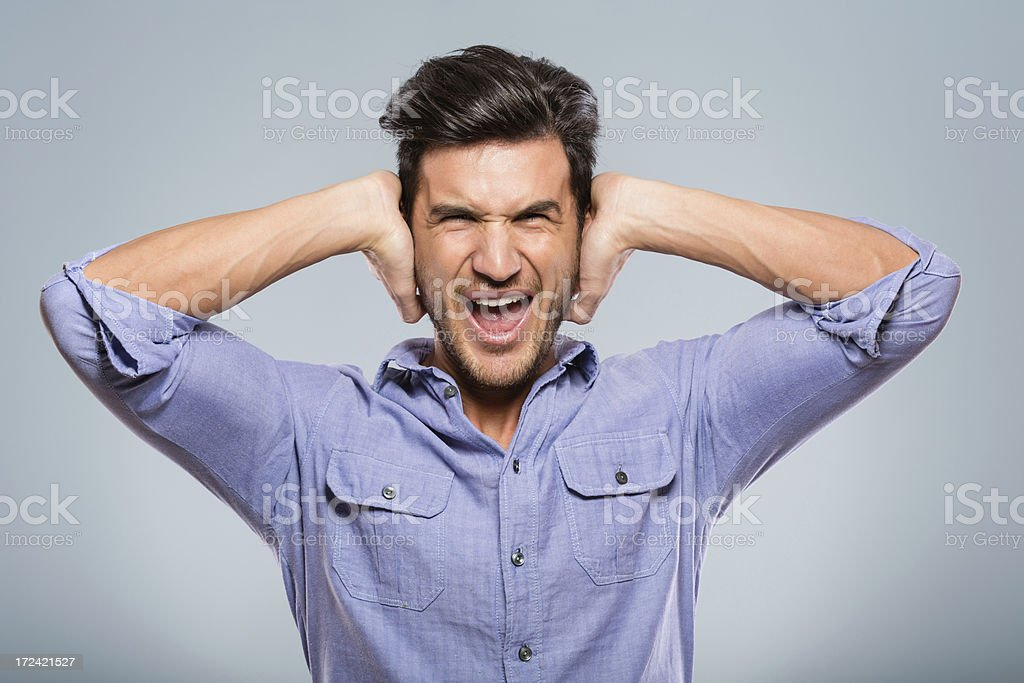 Young man covering his ears royalty-free stock photo