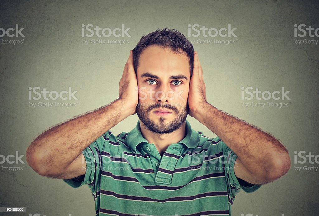 young man covering his ears with hands stock photo