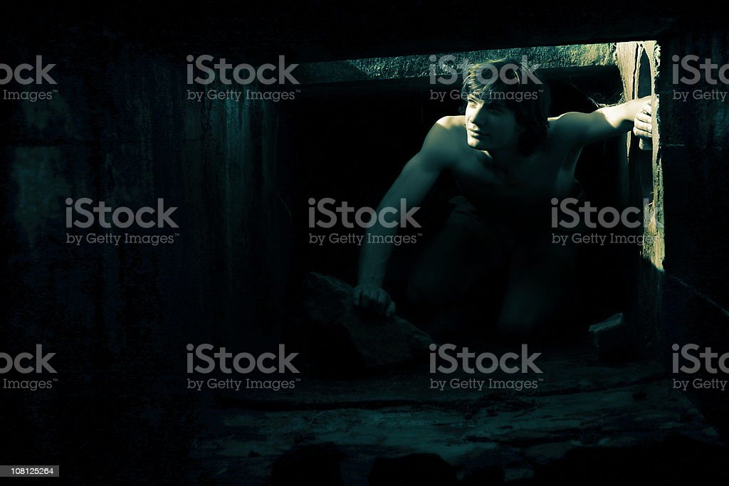 Young Man Crawling Through Small, Dark Tunnel royalty-free stock photo