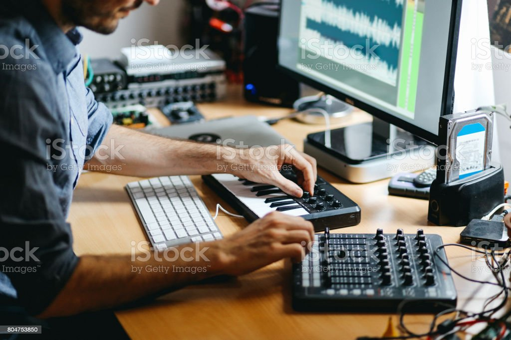 Young man creating music at home stock photo