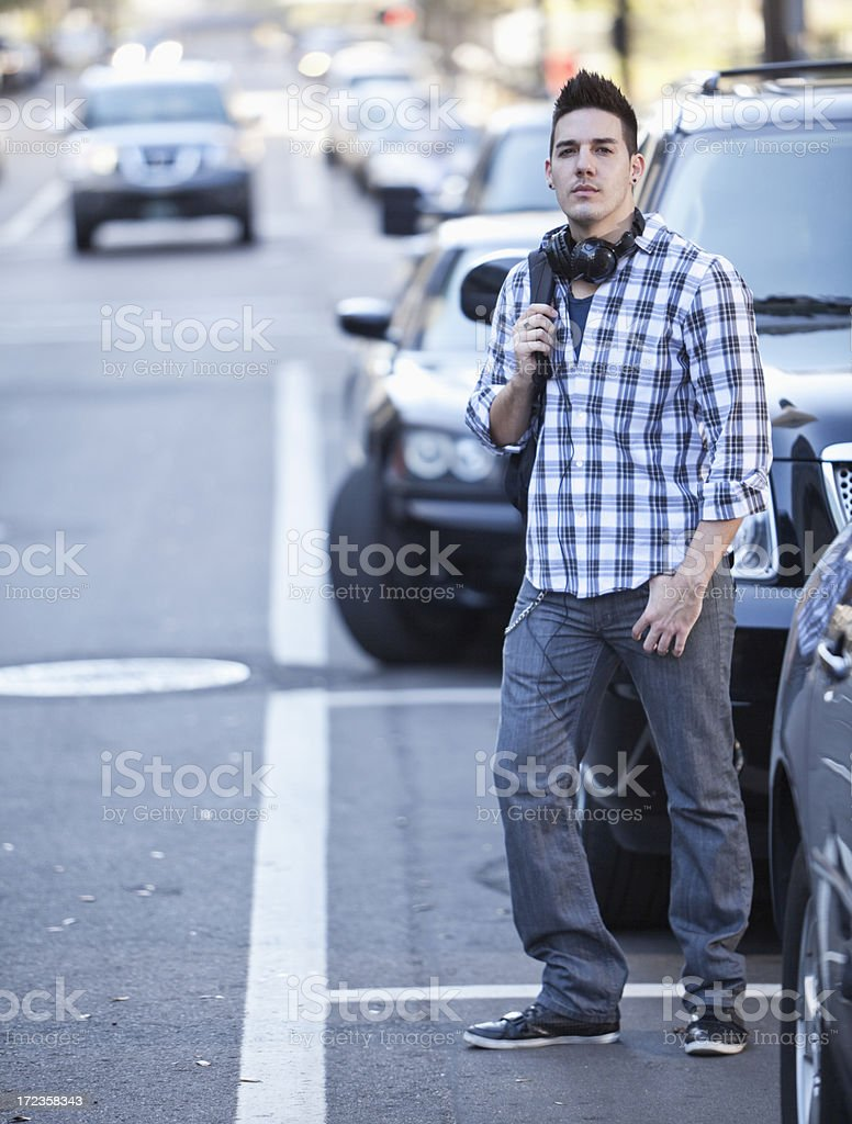 Young man crossing city street stock photo