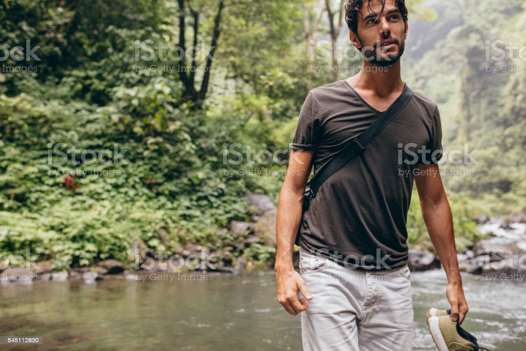 Young man crossing the stream stock photo