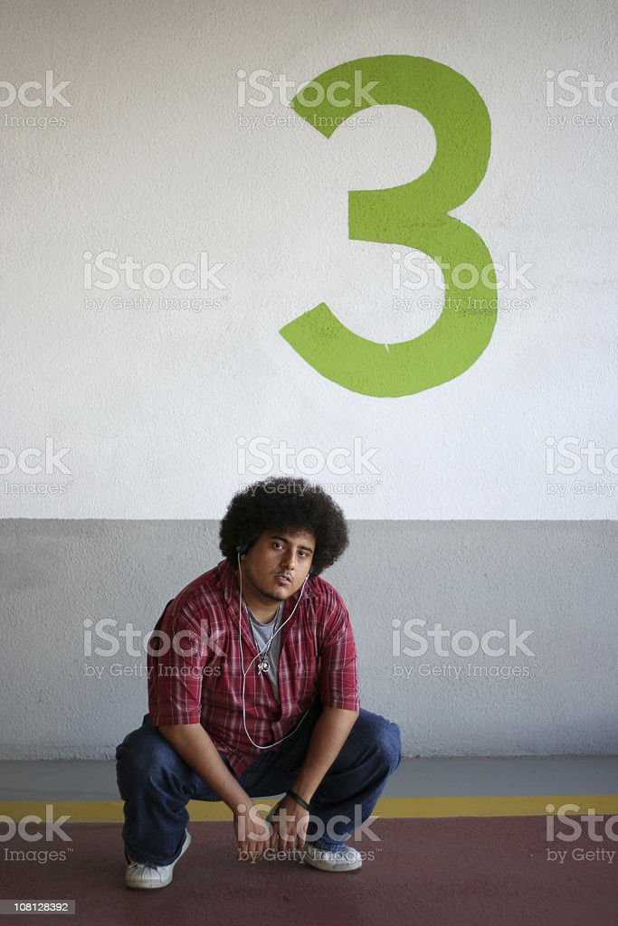 Young Man Crouching Near Number 3 Sign royalty-free stock photo