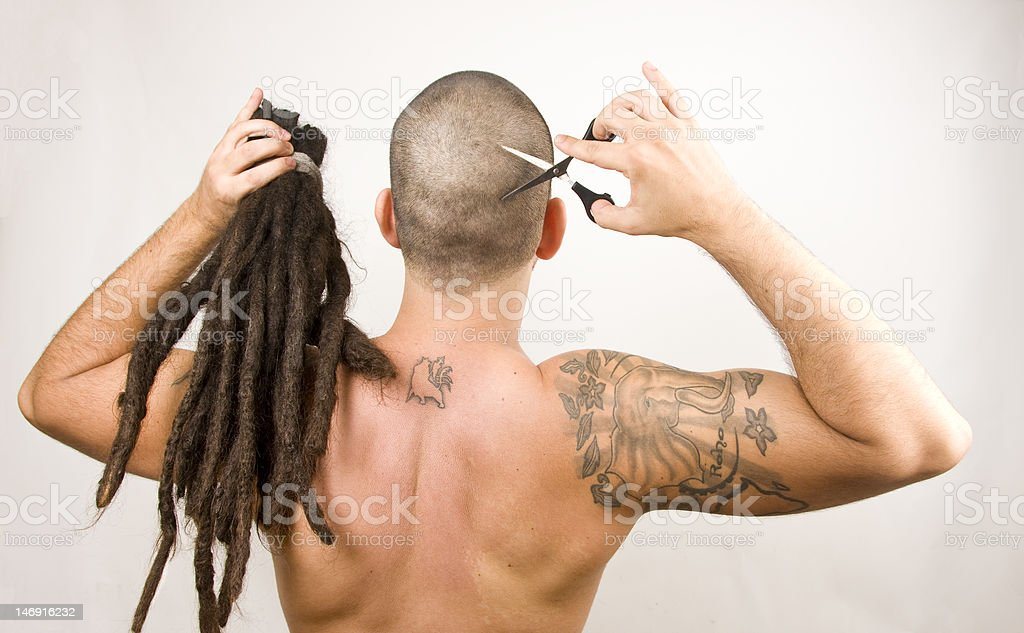 Young man cutting dreadlocks stock photo