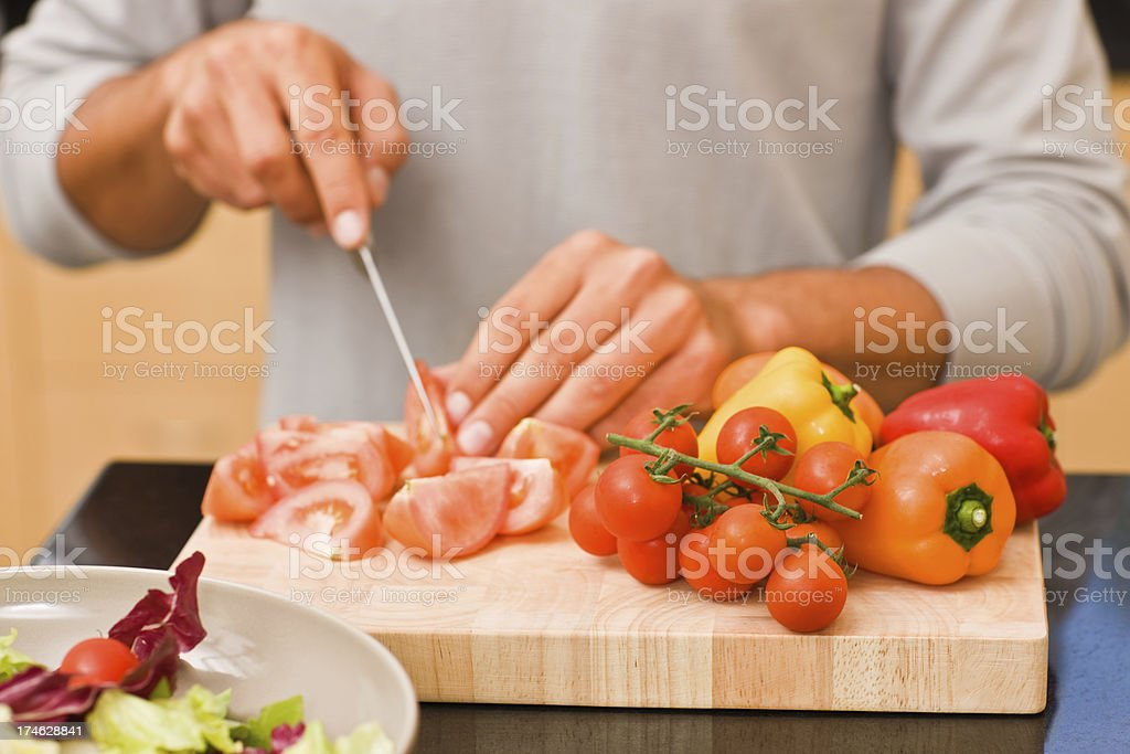 Young man cutting vegetables royalty-free stock photo