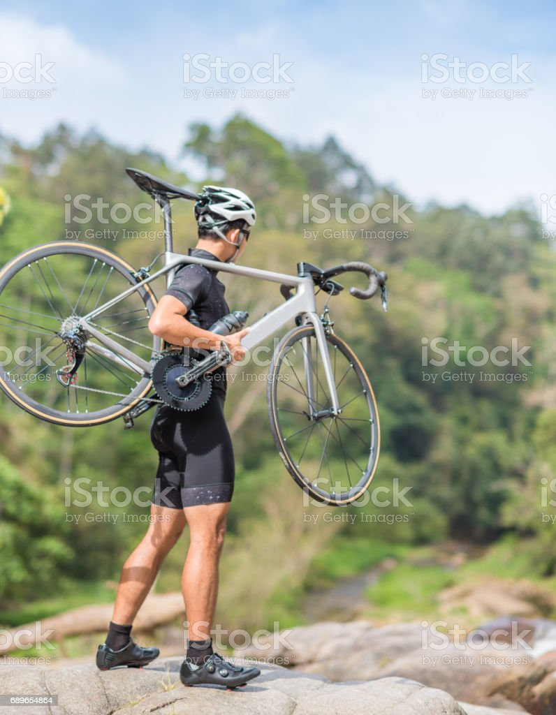 Young man Cyclist riding mountain bike on trail at moring stock photo